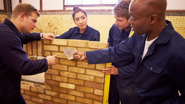 construction teacher and students build wall